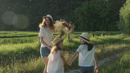 Children three girls in hats holding hands running back along the rural country road, beautiful summer landscapes of nature, golden hour