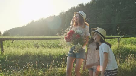 metáfora : Three girls children with bouquet of flowers show finger on the road, emotions joy and happiness, wait and meet, summer nature, country rural background, golden hour