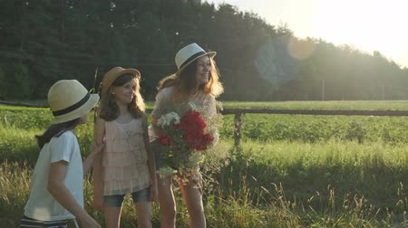 Three girls children with bouquet of flowers show finger on the road, emotions joy and happiness, wait and meet, summer nature, country rural background, golden hour