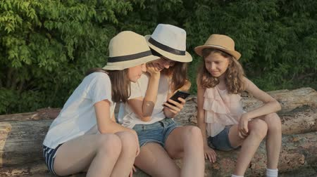 Group of children, three girls sitting on logs in nature and looking at smartphone, girls laughing, golden hour