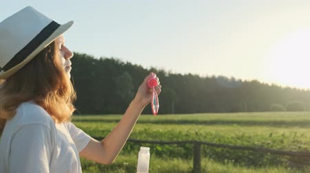 Beautiful girl teenager in a hat blowing soap bubbles, summer nature landscape background, golden hour