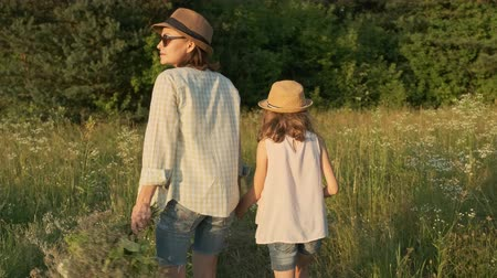 Mother and daughter walking holding hands, back view, summer nature, landscape, golden hour Stok Video