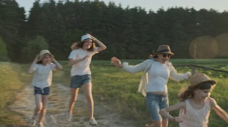 Happy mother and three daughters running along a country road, summer nature background, golden hour