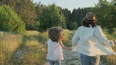Mother and daughter running holding hands, back view, summer nature, landscape, golden hour