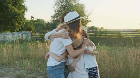Happy mother hugging children, woman with three daughters in nature, background landscape, golden hour