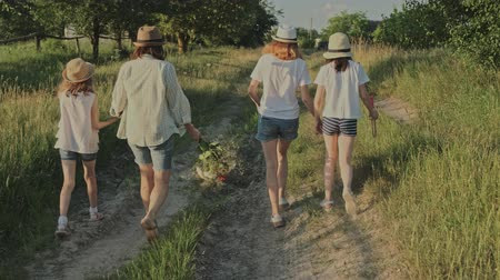 Mother walking with her daughters, woman holding the hand of child, summer natural rural landscape, golden hour Stok Video
