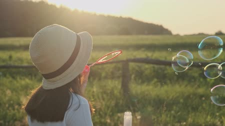 Beautiful child girl in a hat blowing soap bubbles, summer nature landscape background, golden hour