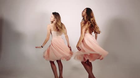 kaštanová : Girls spinning around and volumed skirts rose from wind and from movement of girls. Two beautiful and sweet girls with long hair dancing against grey studio backgound. Concept of shopping.