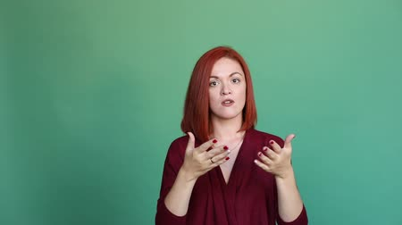 bastante : Angry red haired woman gesturing by hand in camera and talking with unhappy face.