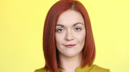 jovial : Gorgeous woman with stylish red hairstyle smiling happily at camera over yellow background.
