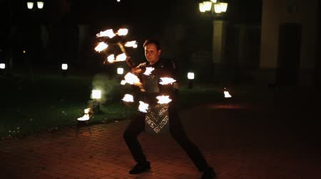 Brave and confident man turning around stick with fire and dancing.