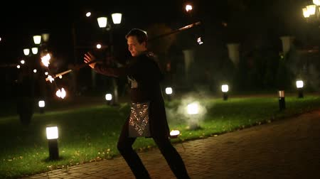 chamejante : Brave and confident man turning around stick with fire and dancing.