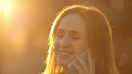 Attractive woman having a conversation via mobile phone in bright sunlight. Stok Video