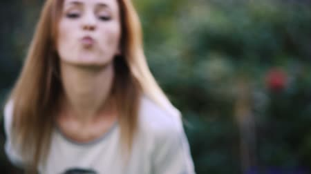 cheerfulness : Pretty girl blowing air kiss at camera in garden. Stock Footage
