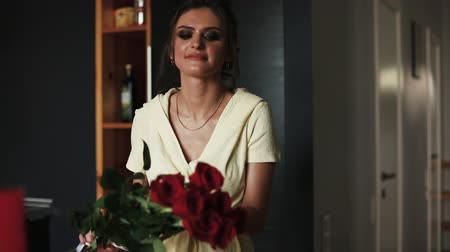 Beautiful and gorgeous woman in bathrobe smelling bouquet of red roses. Dostupné videozáznamy