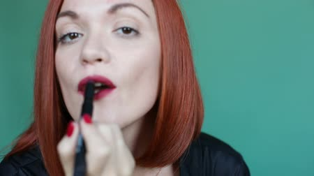 Focus on beautiful and confident red haired woman looking at camera and drawing lips by red lipstick. Pretty female posing in studio on green background and doing makeup for herself.