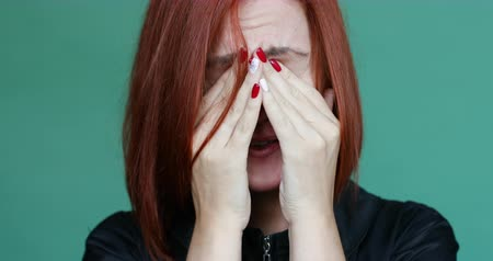 Disappointed and sad red haired woman hiding face by hands and crying.