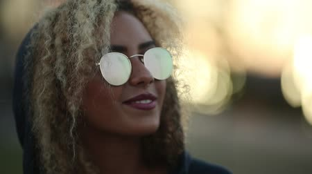 Hipster girl with curly blonde hair and mirrored sunglasses looking away and smiling.
