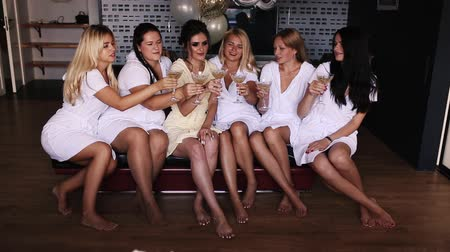 Girls shaking by glasses with champagne on hen party.