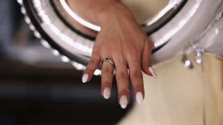Bride showing hand with wedding ring inside festive silver balloon.