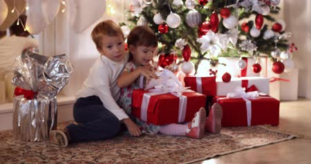 presentes : Children with Christmas presents under the Christmas tree. Stock Footage