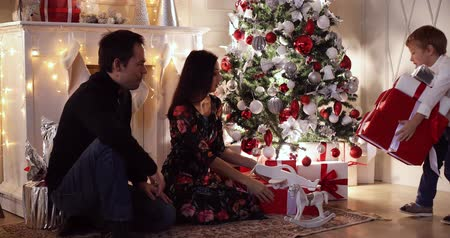 Cheerful parents presenting Christmas presents to their kids by decorated tree.