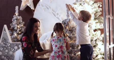 Christmas decorations, family time, child next to the Christmas tree. Kid playing at home. Xmas winter holiday concept. Happy New Year and happy holidays.