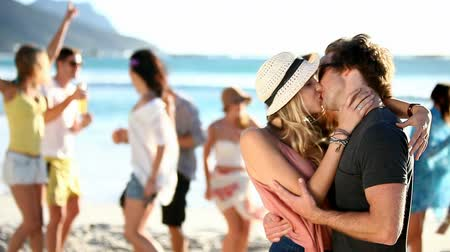 apaixonado : Couple Kissing At A Beach Party, hipster friends dancing in the background Stock Footage