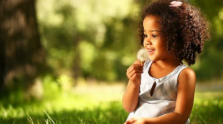 üfleme : Cute little girl having fun blowing Dandelion seeds while relaxing in the park.