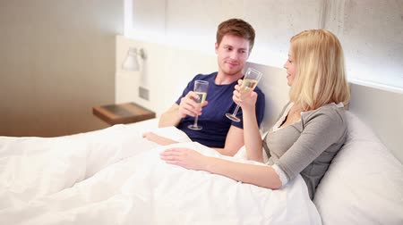 романтика : Young Couple drinking champagne in bed, toasting to each other Стоковые видеозаписи