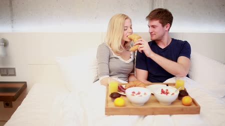 paylaşımı : Young Couple having breakfast in bed, cheerfully sharing a croissant Stok Video