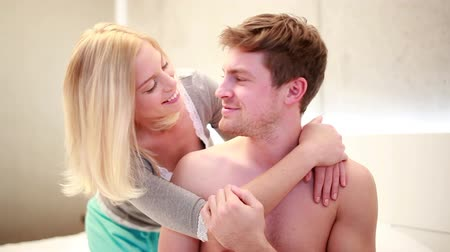 romantic couple : Girlfriend hugs boyfriend on bed from behing, kissing each other Stock Footage