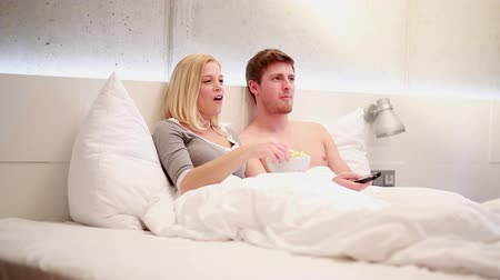 casal heterossexual : Young Couple in bed watching tv and eating popcorn Stock Footage