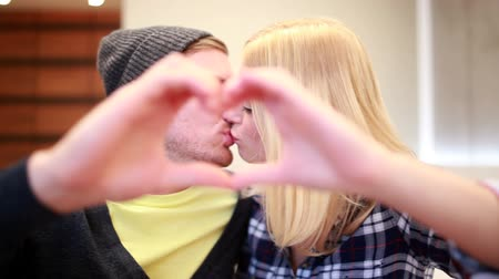 casal heterossexual : Couple kissing make heart-shape with hands