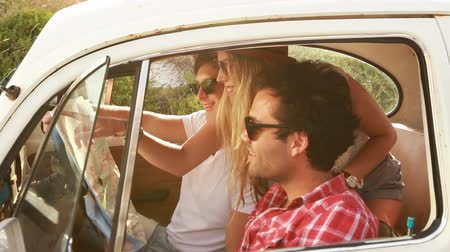 hipster : Young Hipster friends on a roadtrip looking at a map.