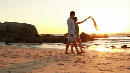romantic couple : Couple in love is walking on the beach at sunset.