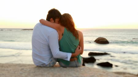 namorado : Couple in love is sitting on a rock near the sea in togetherness at sunset.