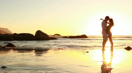 társkereső : Passionate couple holding each other on the beach at sunset.  Stock mozgókép