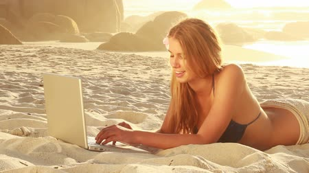 одна молодая женщина только : Beautiful young woman smiling while surfing the net at beach.