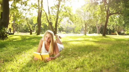 enciclopédia : Portrait of a beautiful young woman smiling with book in garden Stock Footage
