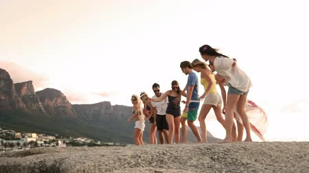 pausa : Young fun party hipster people dancing on a rock at the seaside. Vídeos
