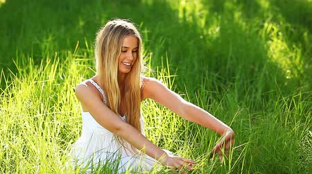 napfény : Smiling young woman touching grass in park. Stock mozgókép