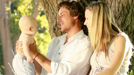 newborn baby : Parents with their baby sitting against tree trunk in the park.  Stock Footage