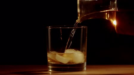 бутылки : Whiskey poured into glass in slow motion Стоковые видеозаписи