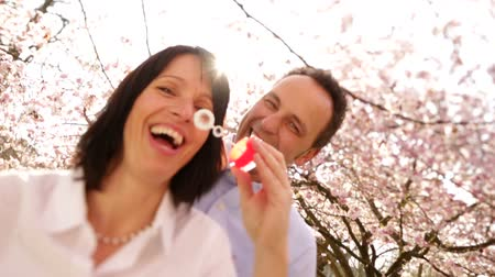 stáří : Attractive mature woman blowing soap bubbles in slow motion with her husband, the happy couple laughing under cherry blossoms