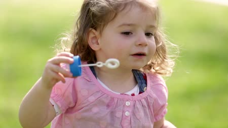 toy : Cute little girl having fun blowing soap bubbles in the park on a sunny day