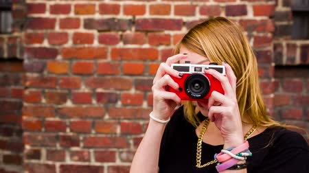 při pohledu na fotoaparát : Hipster girl taking photos with vintage camera in front of brick wall