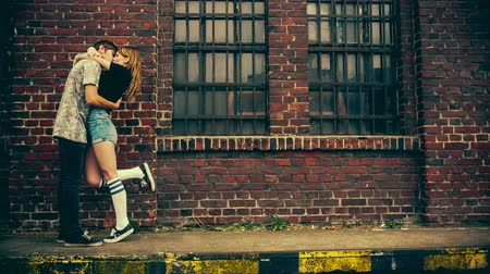 casal heterossexual : Teenage couple kissing in front of old industry building with vintage color correction