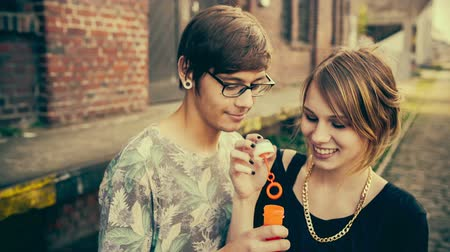 друзья : Teenage hipster couple cheerfully making soap bubbles with vintage color correction