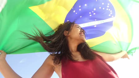 Cheerful girl from brazil with Brazilian flag in slow motion Стоковые видеозаписи